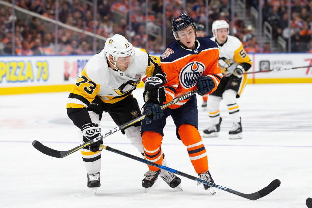 Edmonton Oilers' Kailer Yamamoto (56) battles against Pittsburgh Penguins' Jack Johnson (73) during the second period of an NHL hockey game, in Edmonton, Alberta, Tuesday, Oct. 23, 2018. (Codie McLachlan/The Canadian Press via AP)
