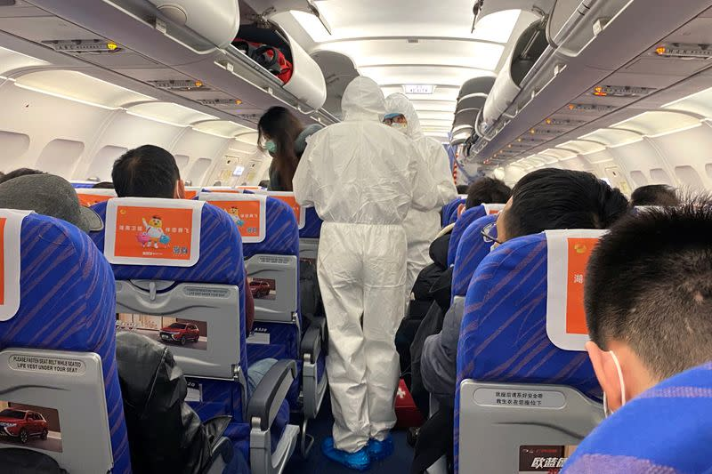 Health workers in protective suits check the condition of a passenger on an airplane that just landed from Changsha, a city in a province neighboring the center of coronavirus outbreak Hubei province, in Shanghai