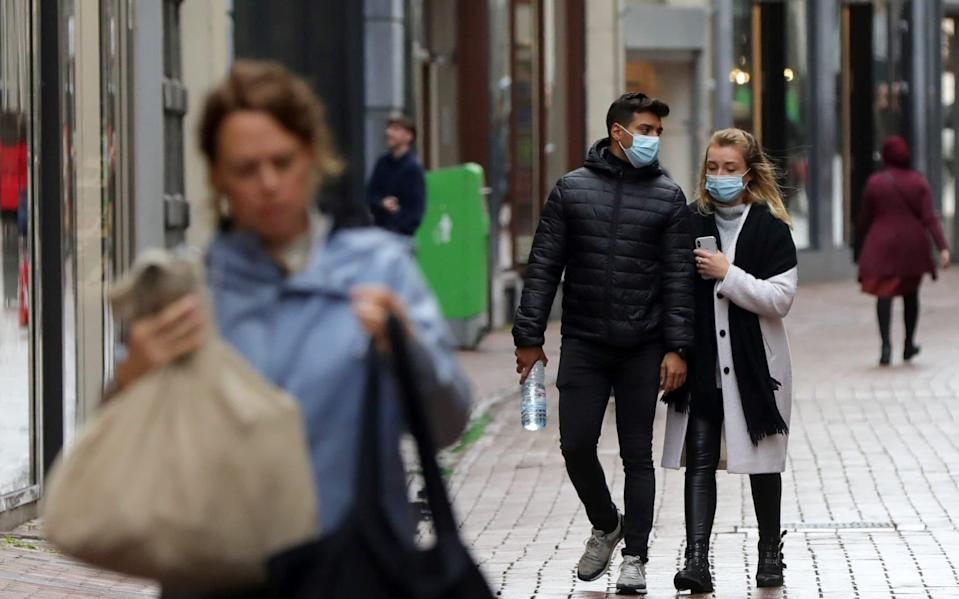 People with and without protective masks walk along the shopping street as the spread of coronavirus continues in Amsterdam - EVA PLEVIER/Reuters