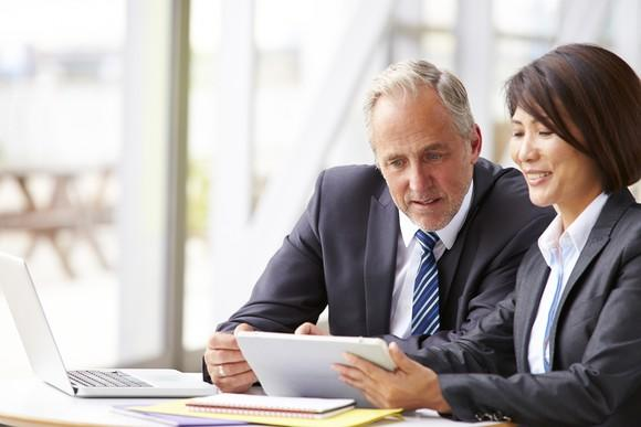 Older man in business suit reviewing document with woman in business suit