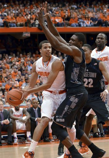 Georgetown's Moses Ayegba, right, forces Syracuse's Michael Carter-Williams to pass during the second half in an NCAA college basketball game in Syracuse, N.Y., Saturday, Feb. 23, 2013. Georgetown won 57-46. (AP Photo/Kevin Rivoli)