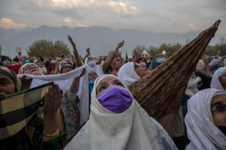 Kashmiri Muslims raise their hands in prayer as a head priest displays a relic, believed to be a hair from the beard of the Prophet Mohammad, at the Hazratbal shrine on Eid-e-Milad, the birth anniversary of the prophet, in Srinagar, Indian controlled Kashmir, Friday, Oct. 30, 2020. (AP Photo/Dar Yasin)