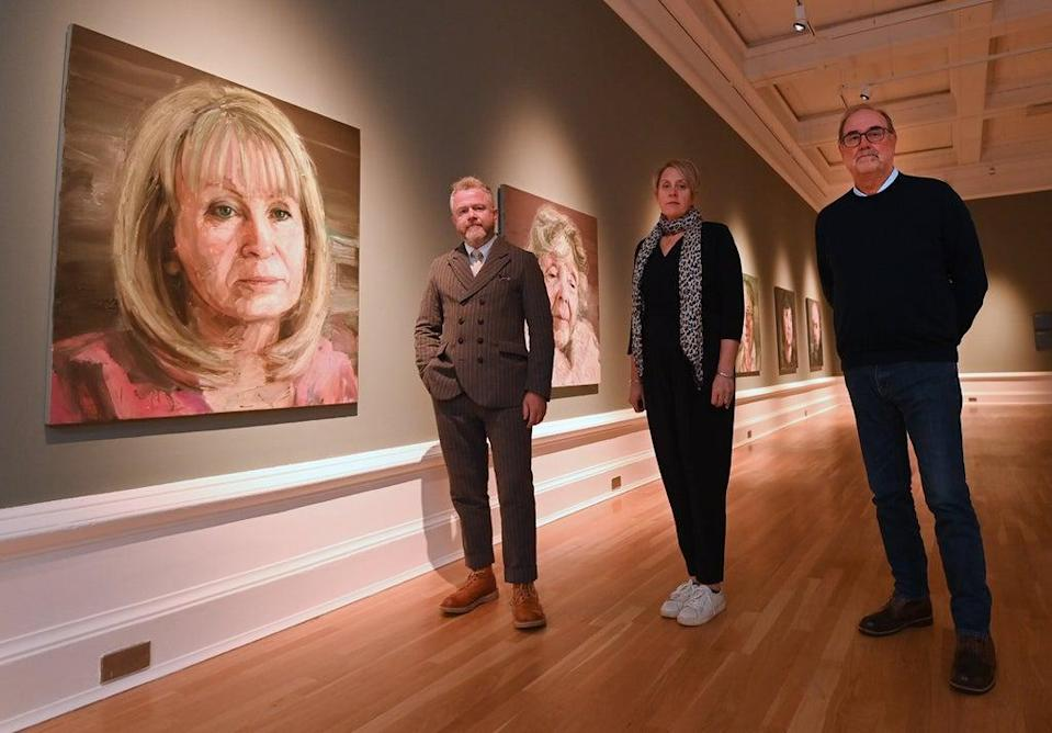 (l-r) With Mo Norton's portrait are artist Colin Davidson, Kathryn Thomson, chief executive of National Museums NI ,and Dennis Godfrey of WAVE (NMNI/PA)