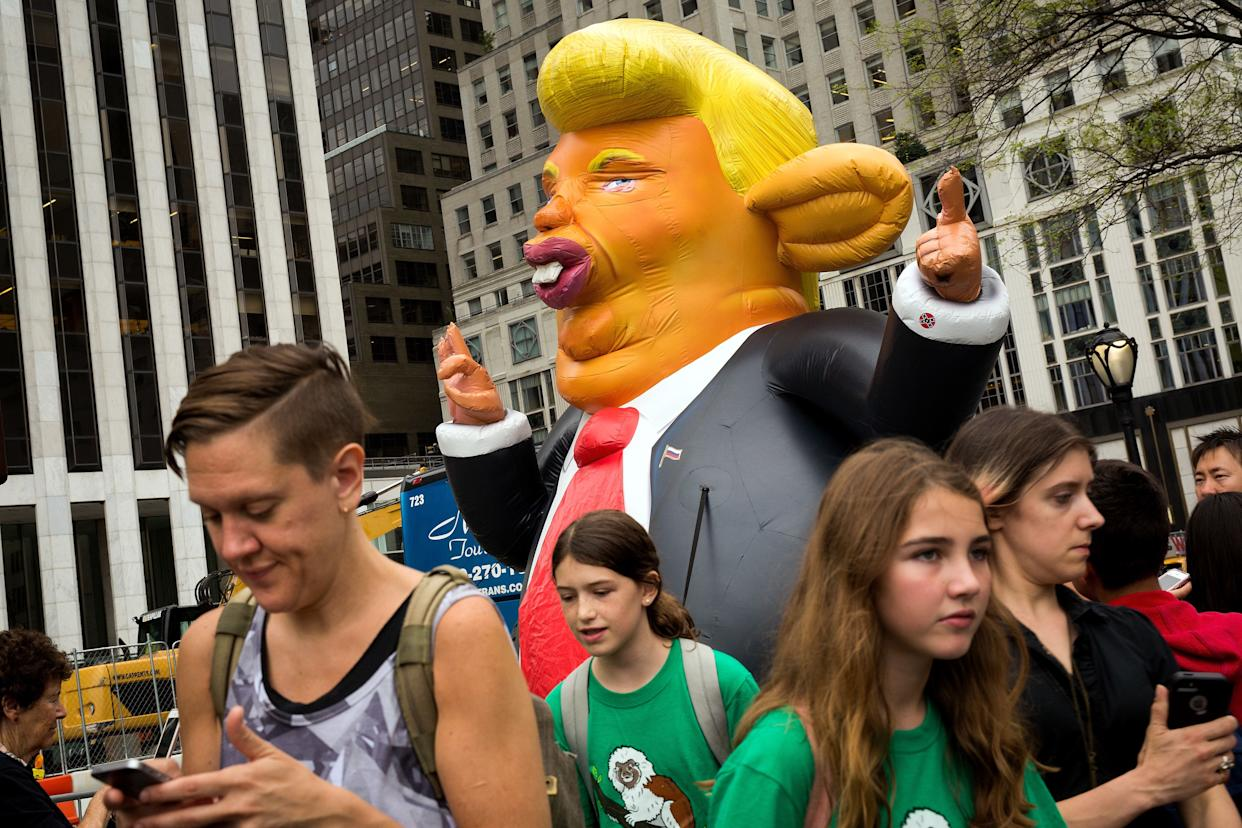 Pedestrians walk past a 15-foot tall inflatable rat in the likeness of U.S. President Donald Trump at the corner of Fifth Avenue and 59th Street up the road from Trump Tower, August 14, 2017 in New York City.