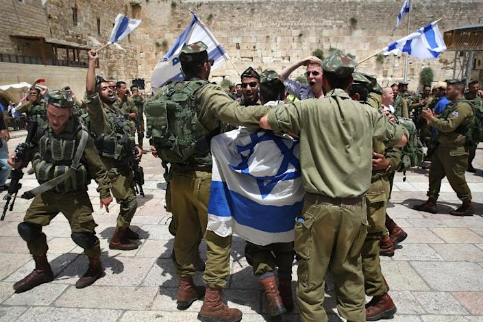 Israeli soldiers dance at the Western Wall in Jerusalem's old city on June 5, 2016 with their national flags as they celebrate the Jerusalem day which marks Israel's 1967 seizure of the Palestinian-dominated eastern half of Jerusalem (AFP Photo/Menahem Kahana)