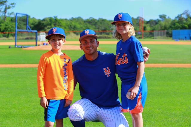 <p>New York Mets player T.J. Rivera poses for a photo with two fans during spring training workouts in Port St. Lucie, Fla., Feb. 23, 2018. The youngsters were given an opportunity to participate in drillls with Rivera. (Photo: Gordon Donovan/Yahoo News) </p>