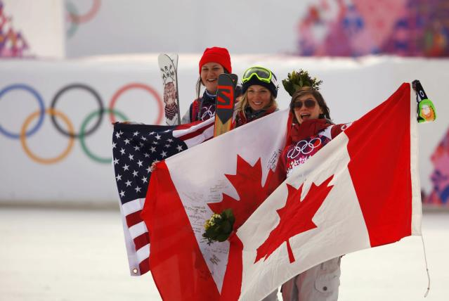 From L-R: Second-placed Devin Logan of the U.S., winner Canada's Dara Howell and third-placed Canada's Kim Lamarre celebrate with their national flags after their women's freestyle skiing slopestyle finals at the 2014 Sochi Winter Olympic Games in Rosa Khutor February 11, 2014. REUTERS/Lucas Jackson (RUSSIA - Tags: SPORT OLYMPICS SPORT SKIING TPX IMAGES OF THE DAY)
