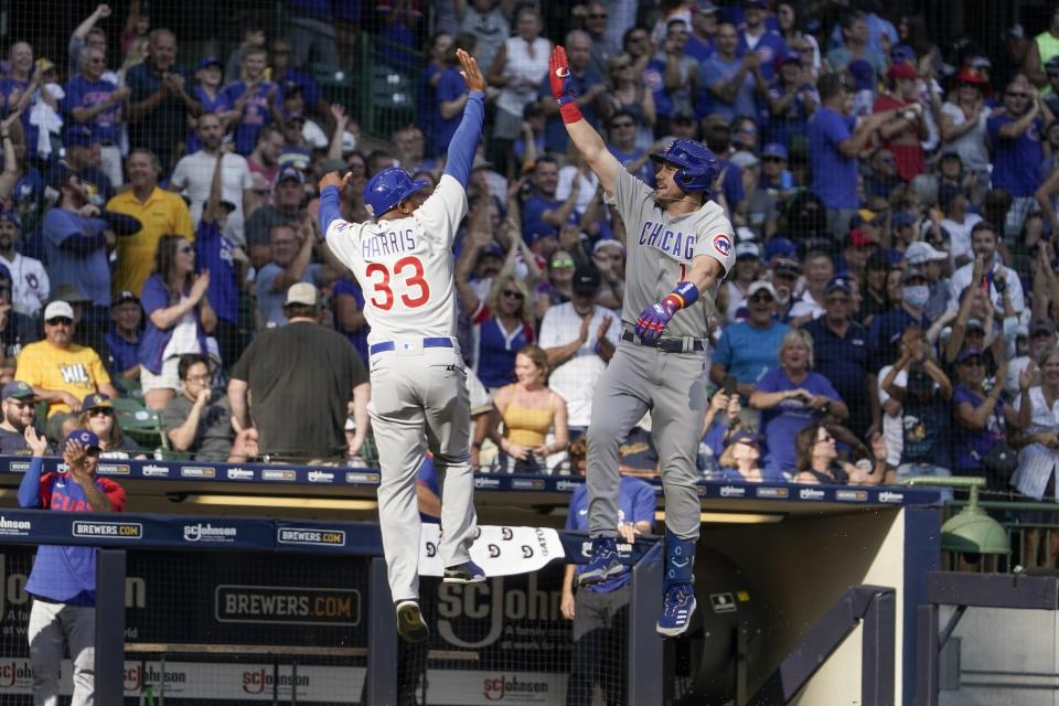 Chicago Cubs' Patrick Wisdom celebrates with third base coach Willie Harris (33) after hitting a three-run home run during the eighth inning of a baseball game against the Milwaukee Brewers Sunday, Sept. 19, 2021, in Milwaukee. (AP Photo/Morry Gash)