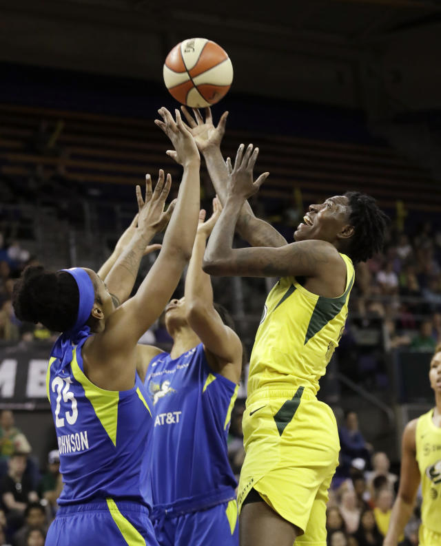 Seattle Storm's Natasha Howard, right, and Dallas Wings' Glory Johnson (25) reach for the ball during the first half of a WNBA basketball game Friday, July 12, 2019, in Seattle. (AP Photo/Elaine Thompson)