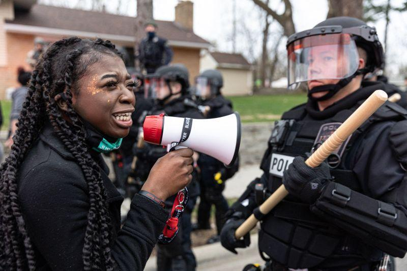 A woman confronts police officers standing in line as protesters gather after an officer shot and killed a black man in Brooklyn Center, Minneapolis, Minnesota on April 11,2021.