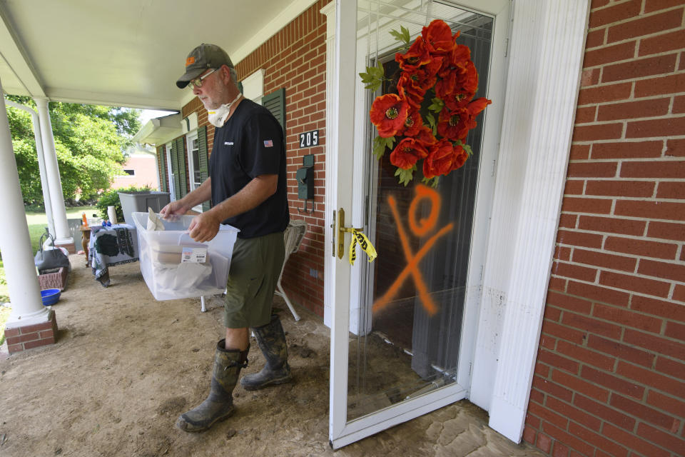 Jason Walker brings items out his aunt's house after recent flooding, Monday, Aug. 23, 2021, in Waverly, Tenn. (AP Photo/John Amis)