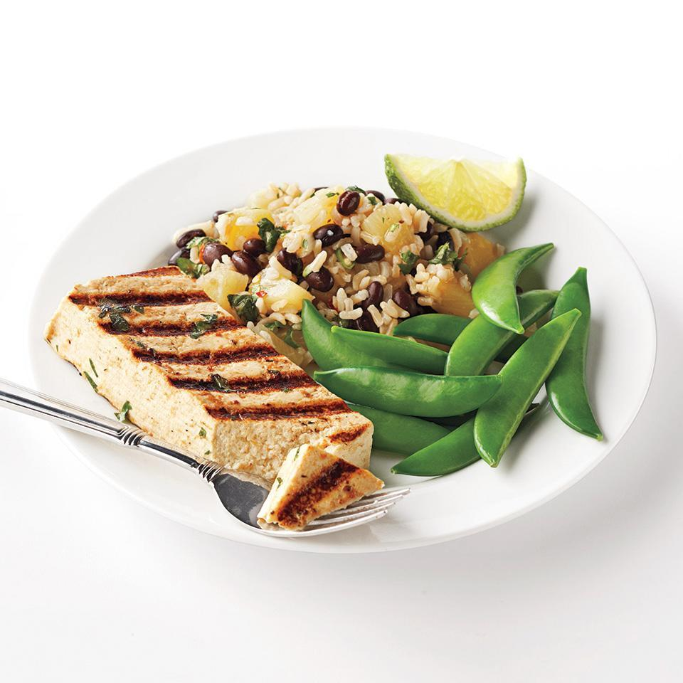 "<p>Grilled slices of tofu are marinated in a pineapple-cilantro mixture and served with black beans and brown rice in this Caribbean-inspired main dish. Be sure to use extra firm tofu to prevent it from breaking apart while cooking this flavorful recipe. <a href=""http://www.eatingwell.com/recipe/266264/caribbean-tofu-with-black-beans-and-rice/"" rel=""nofollow noopener"" target=""_blank"" data-ylk=""slk:View recipe"" class=""link rapid-noclick-resp""> View recipe </a></p>"