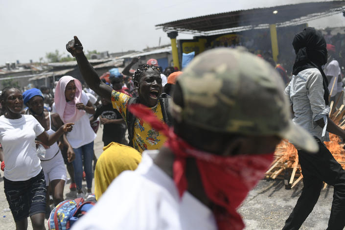 """People, some of them members of the gang led by Jimmy Cherizier, alias Barbecue, a former police officer who heads a gang coalition known as """"G9 Family and Allies,"""" demonstrate around a bonfire during a march to demand justice for slain Haitian President Jovenel Moise in La Saline neighborhood of Port-au-Prince, Haiti, Monday, July 26, 2021. Moise was assassinated on July 7 at his home. (AP Photo/Matias Delacroix)"""