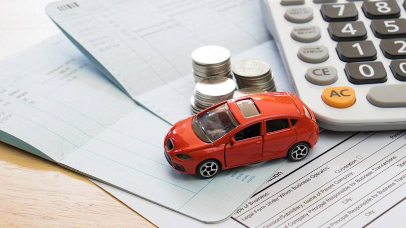 Model car, calculator, money, papers symbolic of car insurance ownership