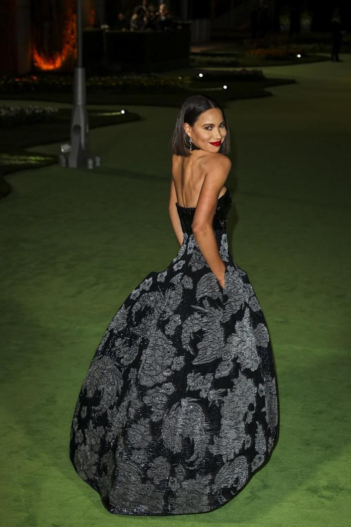 A woman in a patterned, black dress posing on a green carpet