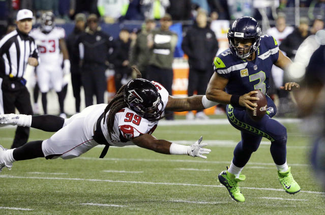 Seattle Seahawks quarterback Russell Wilson (3) scrambles away from a diving Atlanta Falcons defensive end Adrian Clayborn (99) in the first half of an NFL football game, Monday, Nov. 20, 2017, in Seattle. (AP Photo/Ted S. Warren)