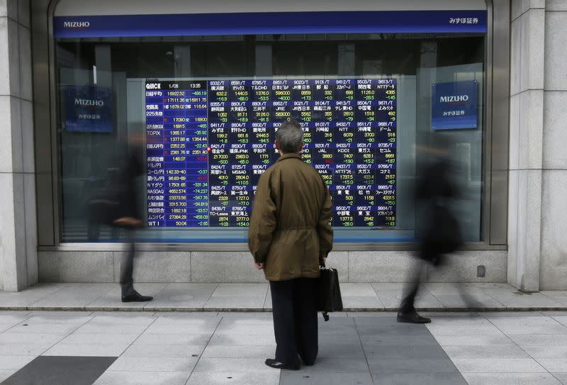 A man looks at an electronic stock quotation board outside a brokerage in Tokyo January 6, 2015. REUTERS/Issei Kato