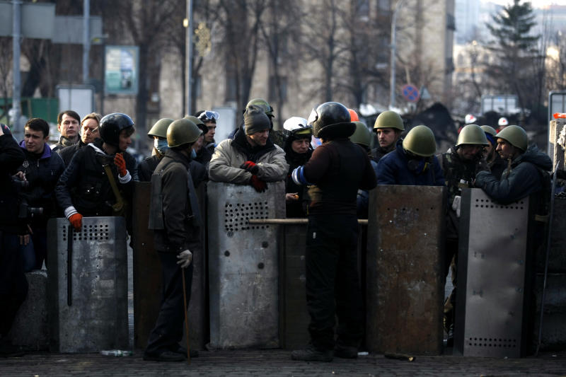 Anti-government protesters man a barricade on the outskirts of Independence Square in Kiev, Ukraine, Friday, Feb. 21, 2014. In a day that could significantly shift Ukraine's political destiny, opposition leaders signed a deal Friday with the country's beleaguered president that calls for early elections, a new constitution and a new unity government. (AP Photo/ Marko Drobnjakovic)