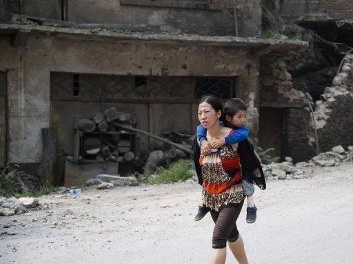 A woman carries her child in Yiliang on September 8 after two quakes hit the border of southwest China on Friday. Some residents have left for nearby shelters, but most had departed before the ambulances, army vehicles and Red Cross jeeps arrived on the scene