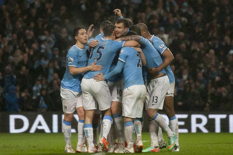 Manchester City's Edin Dzeko, centre, celebrates with teammates after scoring his second goal against Aston Villa during their English Premier League soccer match at the Etihad Stadium, Manchester, England, Wednesday May 7, 2014