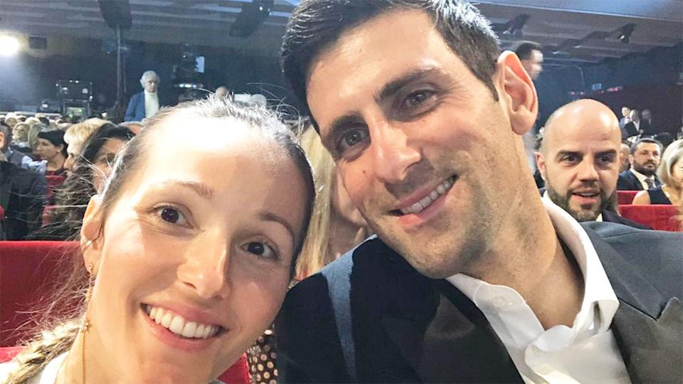 Seen here, Novak Djokovic and his wife Jelena pose together for a photo sitting amongst a crowd of people.