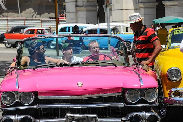 Tourists from the United States sit on an old American car in Havana, on April 6, 2015 (AFP Photo/Yamil Lage)