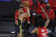 Golden State Warriors guard Stephen Curry, left, shoots against Houston Rockets forward Christian Wood during the second half of an NBA basketball game in San Francisco, Saturday, April 10, 2021. (AP Photo/Jed Jacobsohn)