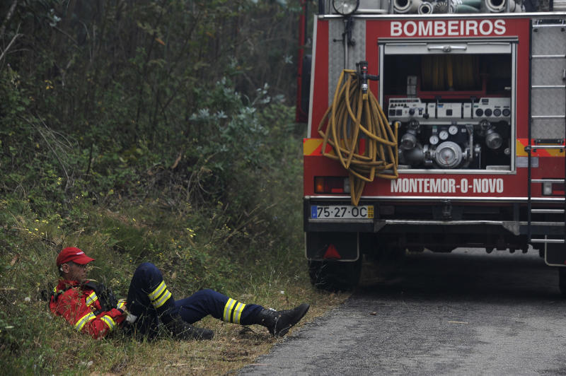 A firefighter from Montemor-o-Novo, southern Portugal, takes a rest by the side of a road in Aguda, outside the village of Figueiro dos Vinhos central Portugal, Monday, June 19, 2017. More than 2,000 firefighters in Portugal battled Monday to contain major wildfires in the central region of the country, where one blaze killed 62 people, while authorities came under mounting criticism for not doing more to prevent the tragedy. (AP Photo/Paulo Duarte)