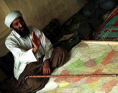 Osama bin Laden is shown sitting in front of a map.