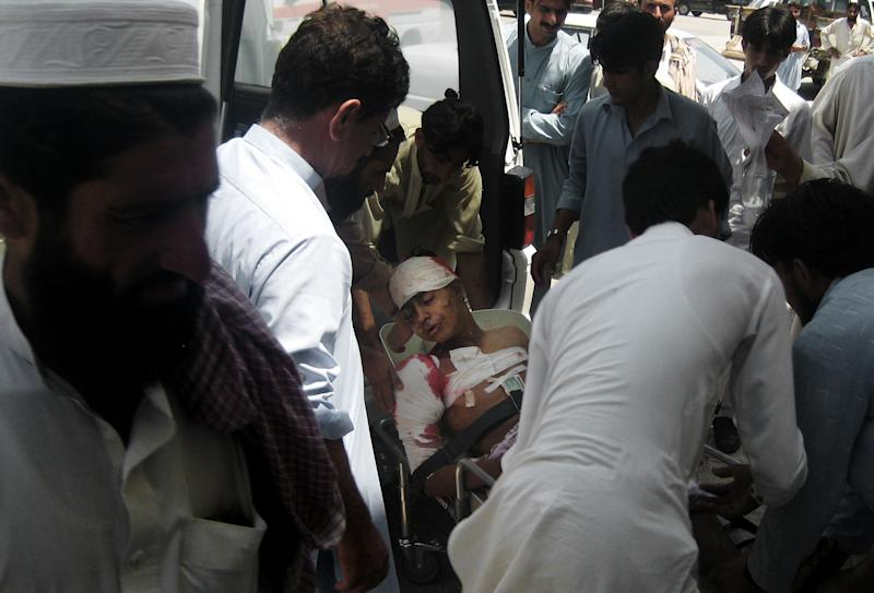 People carry a boy injured from a bomb blast, in the Pakistani tribal area of Khar, Bajur, Thursday, July 26, 2012. A government official says a bomb has exploded in a market in northwestern Pakistan close to the Afghan border, killing scores of people. (AP Photo/Anwarullah Khan)