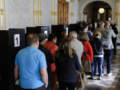 FILE- In this Tuesday, Sept. 19, 2017 file photo, people line up to cast their votes at a polling station for the absentee vote in Berlin, Germany. German voters elect a new parliament on Sunday, Sept. 26, 2021, a vote that will determine who succeeds Chancellor Angela Merkel after her 16 years in power. (AP Photo/Markus Schreiber, File)