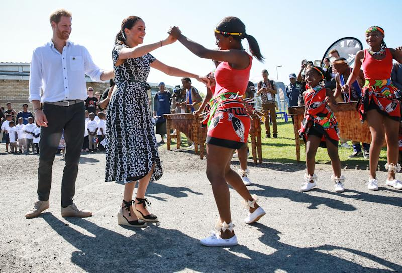 "Prince Harry, Duke of Sussex and Meghan, Duchess of Sussex dance as they arrive for a visit to ""Justice desk"", an NGO in the township of Nyanga in Cape Town, as they begin their tour of the region on September 23, 2019. - Britain's Prince Harry and his wife Meghan arrived in South Africa on September 23, launching their first official family visit in the coastal city of Cape Town. The 10-day trip began with an education workshop in Nyanga, a township crippled by gang violence and crime that sits on the outskirts of the city. (Photo by Betram MALGAS / POOL / AFP) (Photo credit should read BETRAM MALGAS/AFP/Getty Images)"