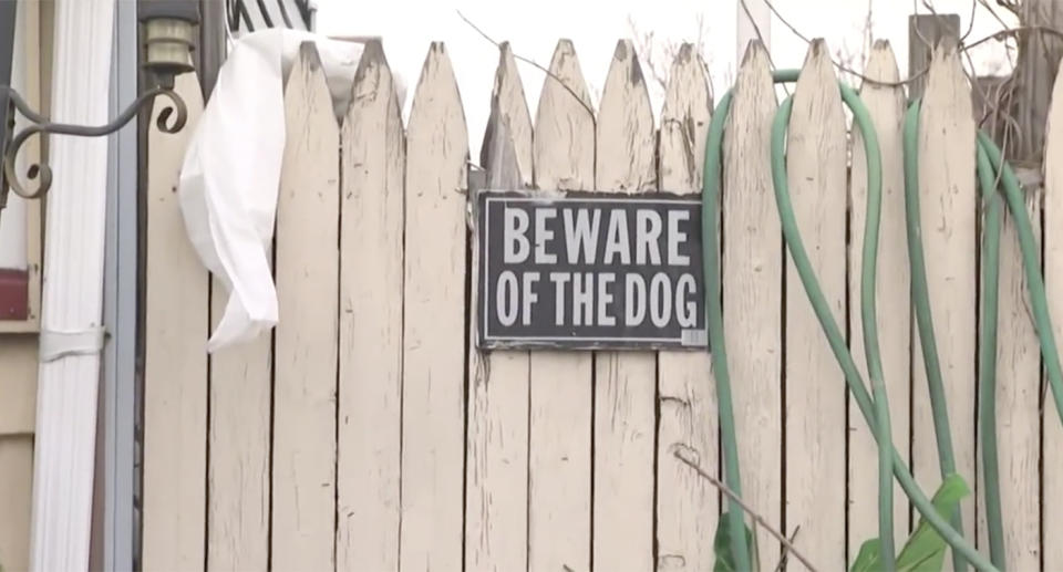 A 'Beware of the dog' sign hangs on a fence.