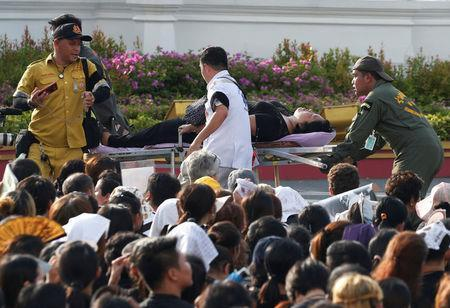 A mourner is attended to after passing out while waiting for the motorcade carrying the body of King Bhumibol Adulyadej outside the Grand Palace in Bangkok, Thailand October 14, 2016. REUTERS/Edgar Su