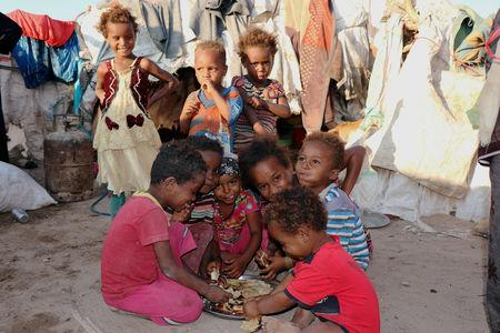 Children eat bread at a camp sheltering displaced people from the Red Sea port city of Hodeidah near Aden, Yemen November 12, 2018. Pictures taken November 12, 2018. REUTERS/Fawaz Salman