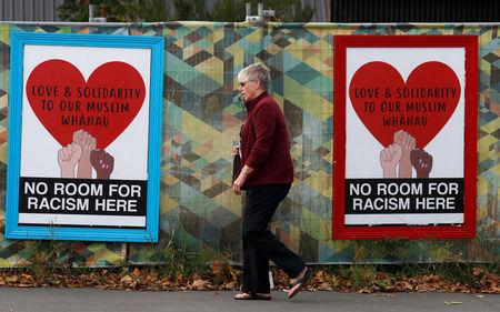 People walk past posters after last Friday's mosque attacks in Christchurch