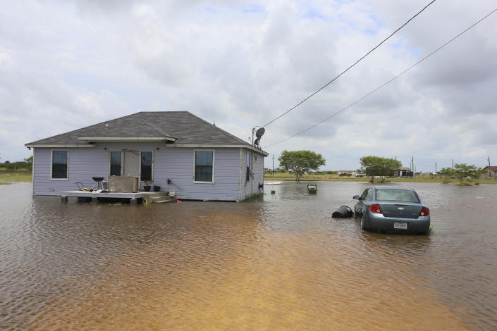 A vehicle sits in more than two feet of floodwater from Hurricane Hanna Monday, July 27, 2020, outside a home on Mescal Street near Laureles, Texas. (Denise Cathey/The Brownsville Herald via AP)
