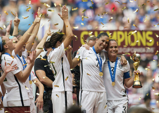 USA teammates Shannon Boxx, second from right, and Christie Rampone, far right, pose with the trophy as the USA team celebrates following their win over Japan at the FIFA Women's World Cup soccer championship in Vancouver, British Columbia, Canada, Sunday, July 5, 2015. (Jonathan Hayward/The Canadian Press via AP)