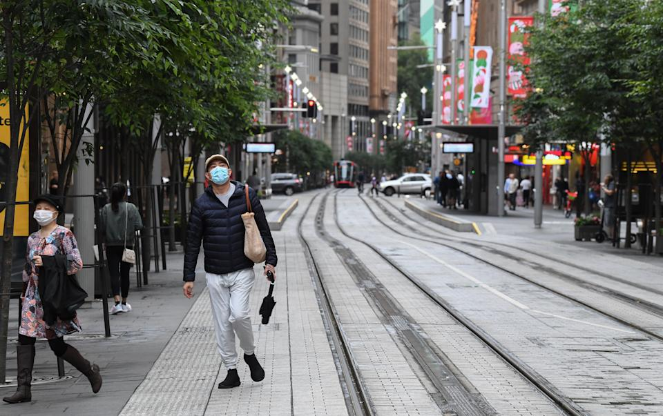 Two people wearing face masks on George Street in the Sydney CBD.
