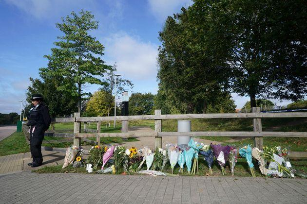 A police officer stands by floral tributes at Cator Park in Kidbrooke, near to the area where the body of Sabina Nessa was found. (Photo: via Associated Press)