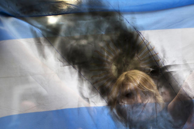 <p>A woman holds up an Argentine flag smeared with black paint, as mourners gather near the funeral home where a private wake is being held for prosecutor Alberto Nisman in Buenos Aires, Argentina, Jan. 28, 2015. On the day after he was found dead in his apartment on Jan. 18, the prosecutor was scheduled to appear before congress to detail his allegations that President Cristina Fernandez had conspired to protect some of the Iranian suspects in the 1994 bombing of a Jewish center. (Photo: Rodrigo Abd/AP) </p>
