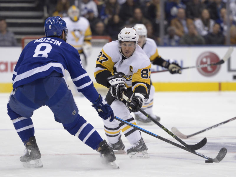 Pittsburgh Penguins center Sidney Crosby (87) and Toronto Maple Leafs defenseman Jake Muzzin (8) vie for the puck during the first period of an NHL hockey game Thursday, Feb. 20, 2020, in Toronto. (Nathan Denette/The Canadian Press via AP)