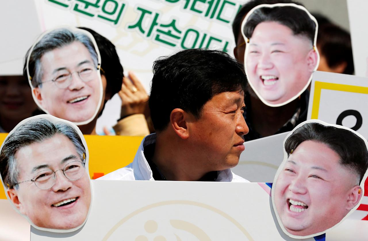 A participant stands among cutouts of South Korea's President Moon Jae-in and North Korea's leader Kim Jong Un during a pro-unification rally ahead of the upcoming summit between North and South Korea in Seoul, South Korea April 25, 2018.  REUTERS/Jorge Silva     TPX IMAGES OF THE DAY