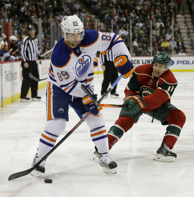 Edmonton Oilers center Sam Gagner (89) controls the puck in front of Minnesota Wild left wing Zach Parise (11) during the second period of an NHL hockey game in St. Paul, Minn., Tuesday, March 11, 2014. (AP Photo/Ann Heisenfelt)