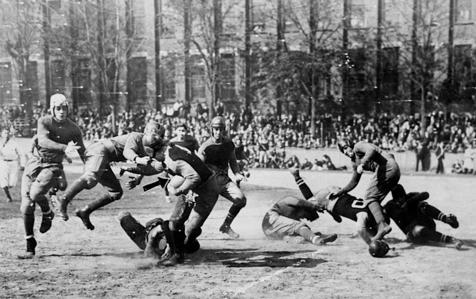 Players in leather helmets tackle a running back circa 1920