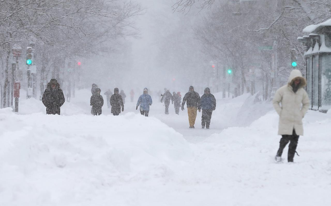 BOSTON, MA - FEBRUARY 09:  People walk in the snow during a lingering blizzard on February 9, 2013 in Boston, Massachusetts. The powerful storm has knocked out power to 650,000 and dumped more than two feet of snow in parts of New England.  (Photo by Mario Tama/Getty Images)