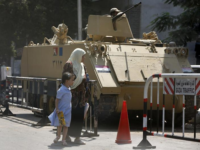 People walk past Egyptian soldiers on an armored personnel carrier in Cairo, Egypt, Tuesday, Sept. 10, 2013. The Egyptian Amy has maintained a presence on the streets since the July ouster of President Mohammed Morsi. (AP Photo/Lefteris Pitarakis)
