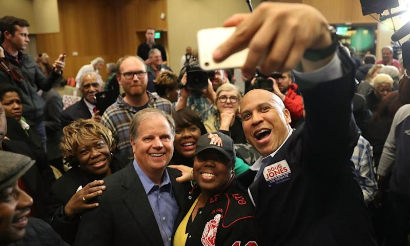 Doug Jones takes a picture with Senator Cory Booker of New Jersey and Representative Terri Sewell of Alabama, among supporters at Alabama State University in Montgomery.
