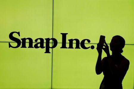 A woman stands in front of the logo of Snap Inc. on the floor of the New York Stock Exchange (NYSE) while waiting for Snap Inc. to post their IPO, in New York City