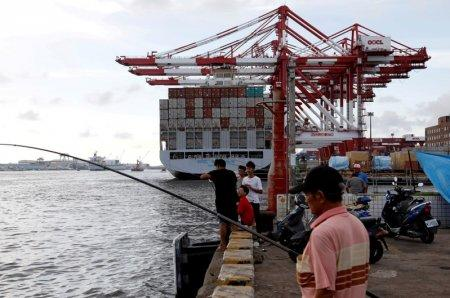 FILE PHOTO: People fish in front of an Orient Overseas Container Line container ship, at Kaohsiung Port, Taiwan August 7, 2017. REUTERS/Tyrone Siu/File Photo